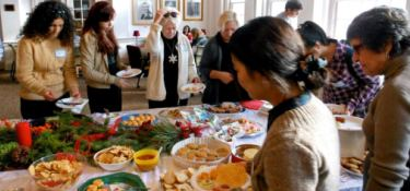 Community Friends and their international students tasting holiday food at the MIFP Holiday Party.